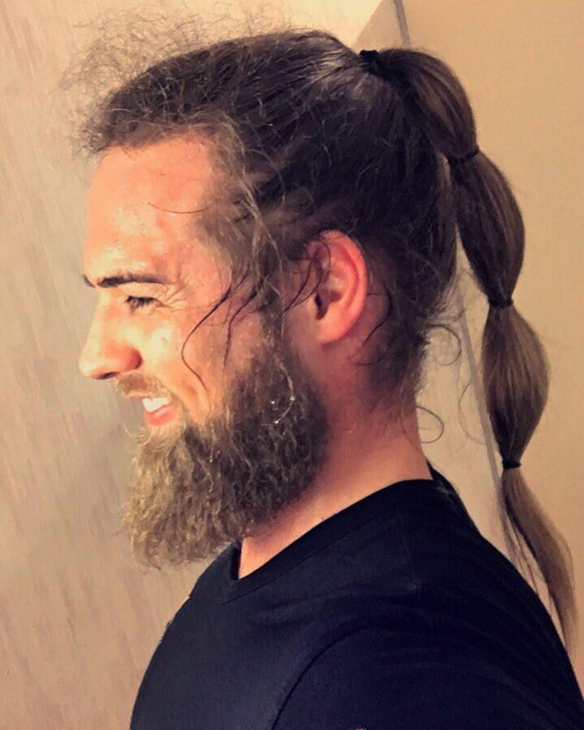 Hombre con barba y trenza larga en el pelo
