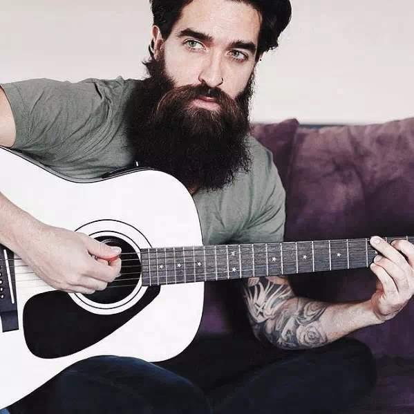 Barba bien larga y grande en hombre moderno con guitarra