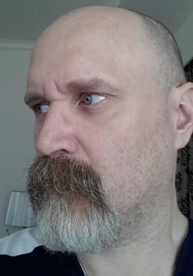 Barba de candado bien larga con canas en hombre calvo