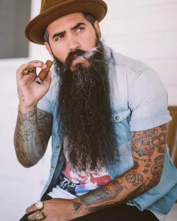 Barba larga sin arreglar en hombre fumando