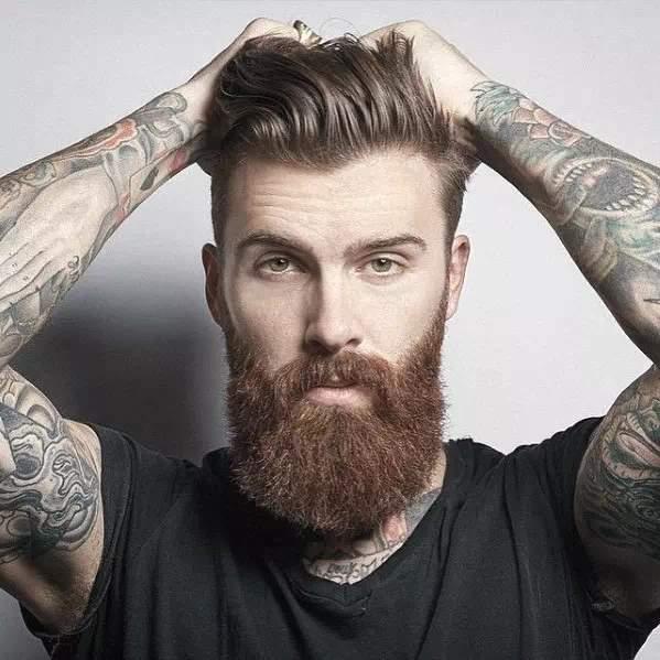 Hombre con barba larga arreglada y un corte de pelo moderno
