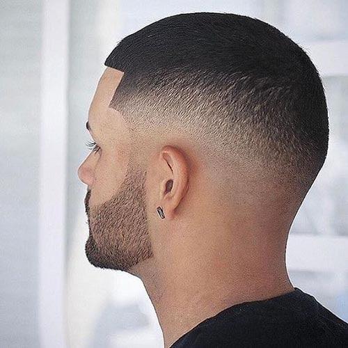 Corte de de cabello rapado con degradado a los lados y cortes