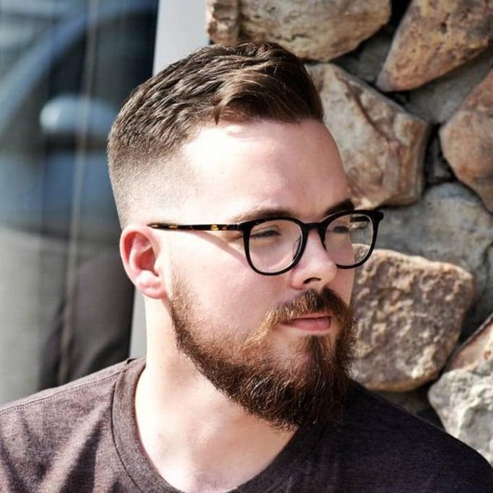 Corte de pelo con degradado a los lados con barba tupida corta