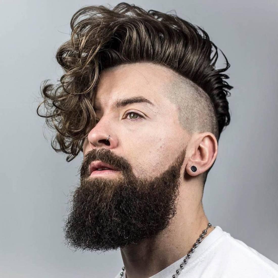 peinado en pelo rizado largo en hombre joven rebajado a un lado